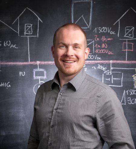 Porträtaufnahme von Lukas Hüppi, Projektleiter Photovoltaik & Speicher bei Reech, vor dunkler Wand