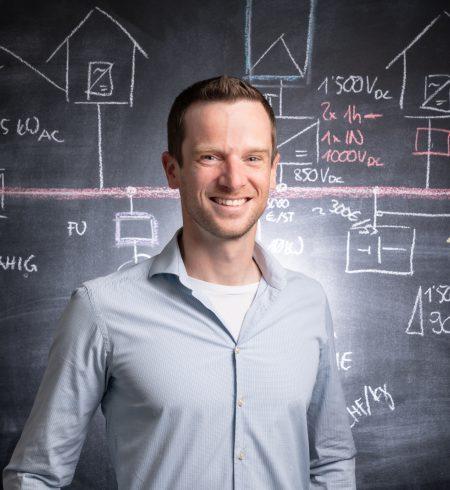 Porträtaufnahme von Martin Fäh, Projektleiter Photovoltaik und Entwicklung, vor dunkler Wand