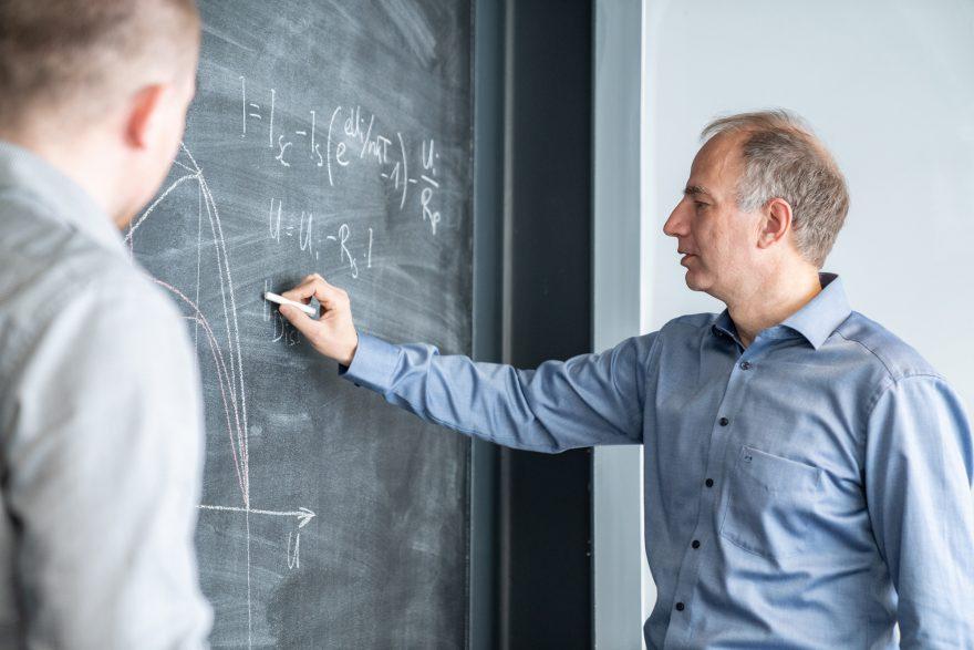 Tamás Szacsvay erklärt Lukas Hüppi die Kennlinienberechnung eines Photovoltaikmoduls an einer Wandtafel