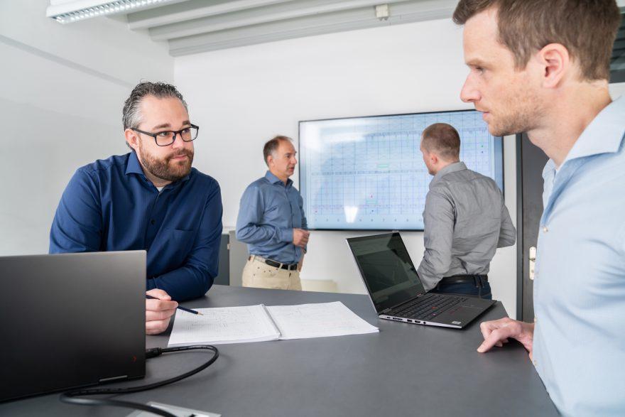 Das Team der Reech GmbH bespricht sich vor einem grossen Bildschirm