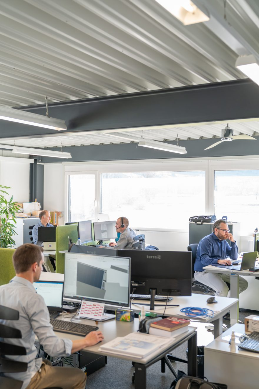 Alle Mitarbeite der Reech gmabh arbeiten an ihren Arbeitsplätzen in einem Grossraumbüro
